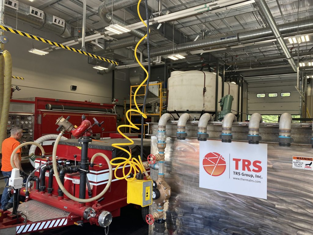 TRS employee Greg Knight (left) monitors the PerfluorAd™ AFFF treatment system as it works to remove PFAS from firefighting vehicle rinsate at a fire station in New England.