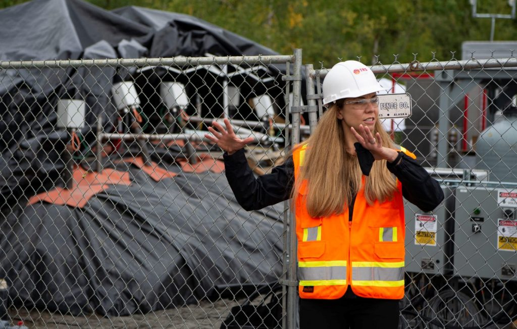 Emily Crownover, Managing Principal Engineer, leads a tour at Eielson Air Force Base in Fairbanks, Alaska, where TRS is using its thermal conduction heating technology on PFAS containing ex situ soil stockpiles (pictured in the background).